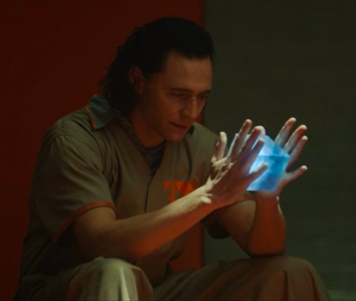Image of Loki in his TVA uniform, holding the tesseract